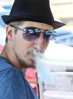 uomo che indossa cappello fedora espira la nebbia vapore foto