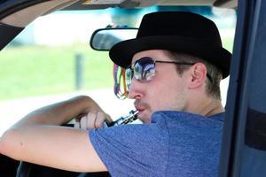 uomo che indossa cappello e occhiali da sole inala dal dispositivo di sigaretta elettronica foto