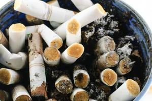 colpo del primo piano delle estremità di sigaretta bruciate foto