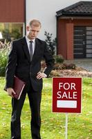 agente immobiliare in piedi davanti a casa foto