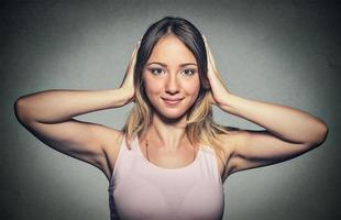 donna felice che copre con le mani le orecchie foto