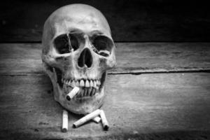 teschio con sigarette, natura morta. foto