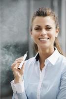 Ritratto di giovane donna che fuma sigaretta elettronica all'aperto foto