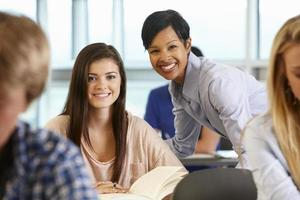 un giovane insegnante che aiuta uno studente mentre entrambi sorridono in classe foto