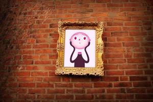 sollevatore capo nella cornice dorata sul muro di mattoni foto