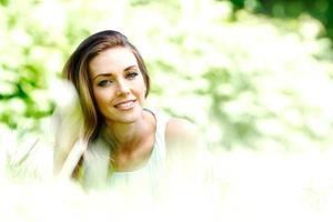 giovane donna in abito blu sdraiato sull'erba foto