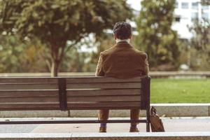 uomo che si distende su una panchina del parco foto
