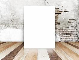 poster in bianco nel muro di mattoni crepa e pavimento in legno tropicale foto