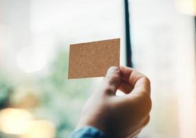 mano dell'uomo con il biglietto da visita artigianale sullo sfocato foto