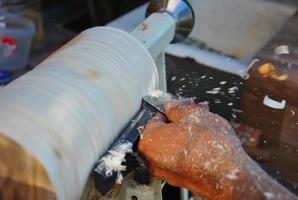 il carpentiere lavora con scalpello sul tornio foto