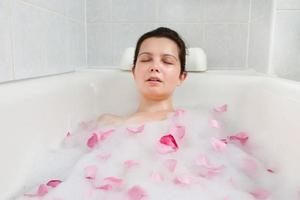 donna che si distende nella vasca da bagno foto