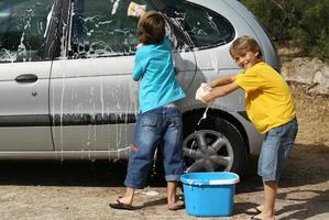 bambini o bambini che lavano la macchina facendo le faccende foto