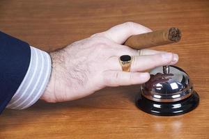 uomo d'affari che suona una campana di servizio. foto