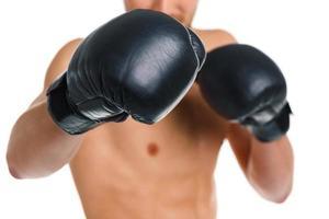 uomo atletico che indossa guantoni da boxe sul bianco foto