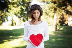 giovane donna con un cartello del cuore foto