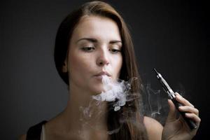 sigaretta elegante di fumo della donna elegante con fumo foto