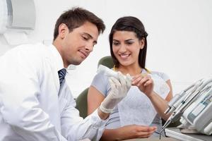 dentista che prescrive dentifricio al paziente foto