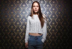 Ritratto di giovane donna in piedi contro il muro scuro. foto