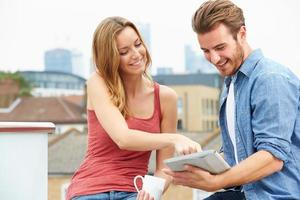 coppia sulla terrazza sul tetto utilizzando la tavoletta digitale foto