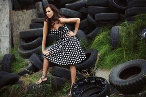 donna ispanica in abito a pois sul mucchio di pneumatici erbosi foto