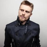 elegante giovane uomo bello in cappotto nero. ritratto in studio moda.