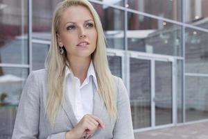 donna di affari premurosa che osserva via contro l'edificio per uffici foto