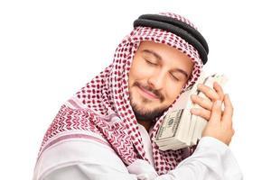 giovane maschio arabo persona che dorme sul denaro foto