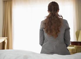 donna d'affari seduto sul letto nella camera d'albergo. retrovisore foto