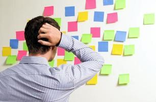 uomo d'affari guardando le note adesive con le mani dietro di lui foto