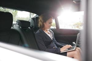 donna di affari che lavora al computer portatile dentro un'automobile