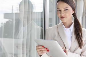 Ritratto di imprenditrice fiduciosa utilizzando la tavoletta digitale foto