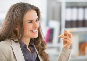 Ritratto di donna d'affari sorridente seduto in ufficio foto