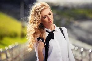 donna d'affari di moda giovane con occhiali da sole sulla strada della città foto