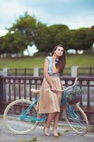 giovane donna bellissima, elegantemente vestita con la bicicletta foto