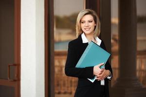 donna d'affari felice con una cartella presso l'edificio per uffici foto