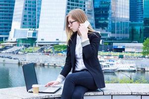 donna di affari che scrive sul computer portatile e che parla sul telefono foto