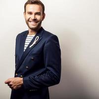 elegante giovane uomo bello e positivo in costume blu scuro. foto