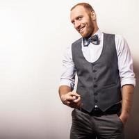 elegante giovane uomo bello in gilet grigio e cravatta a farfalla. foto