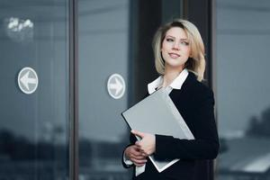giovane imprenditrice con una cartella contro le finestre degli uffici foto