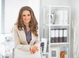Ritratto di donna d'affari felice in piedi in ufficio foto