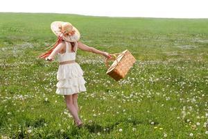 giovane donna che cammina nel campo erboso con cestino da picnic foto
