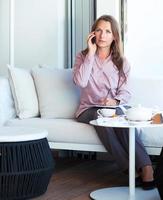 imprenditrice parlando al cellulare in un caffè foto