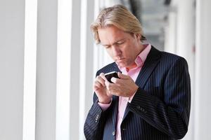 uomo di affari che chiama con il suo cellulare in ufficio bianco. foto