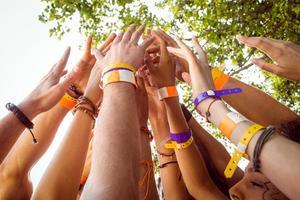 le persone con braccialetti che tengono le mani in alto foto