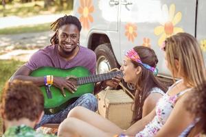 hipster felice sorridendo alla telecamera a suonare la chitarra
