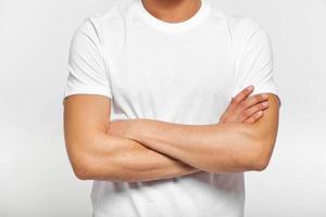 uomo in maglietta bianca con le braccia conserte foto