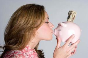 donna che bacia salvadanaio foto