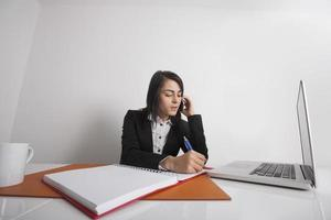 donne di affari che scrivono le note mentre usando il telefono cellulare alla scrivania foto