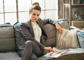 donna di affari che si siede sul sofà in appartamento e che osserva rivista foto