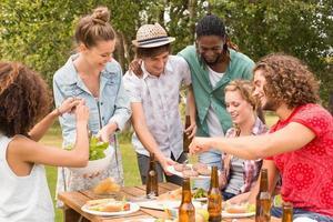 amici felici nel parco pranzando foto